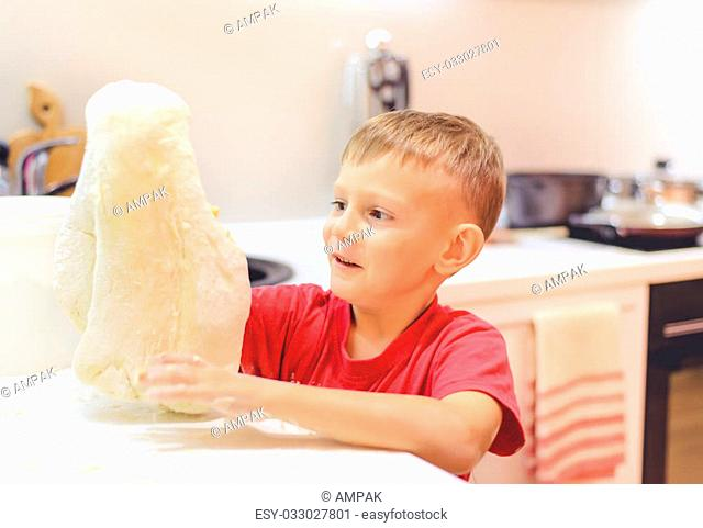 Little boy having fun playing with dough in the kitchen standing at the counter kneading it with his fingers, close up view