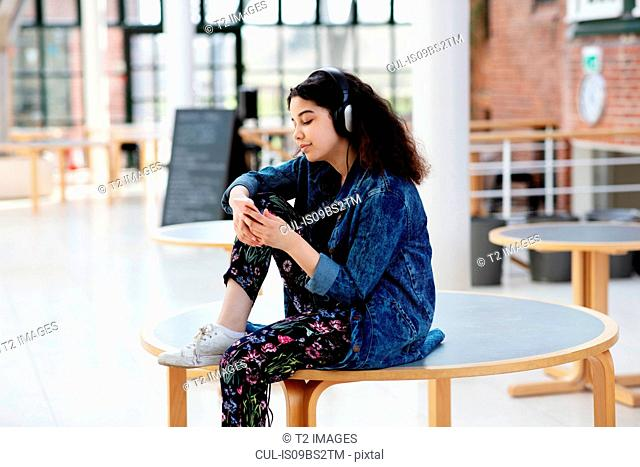 Teenage girl using headphones in school