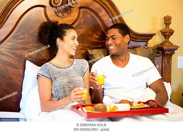 Couple sitting in bed having breakfast face to face smiling