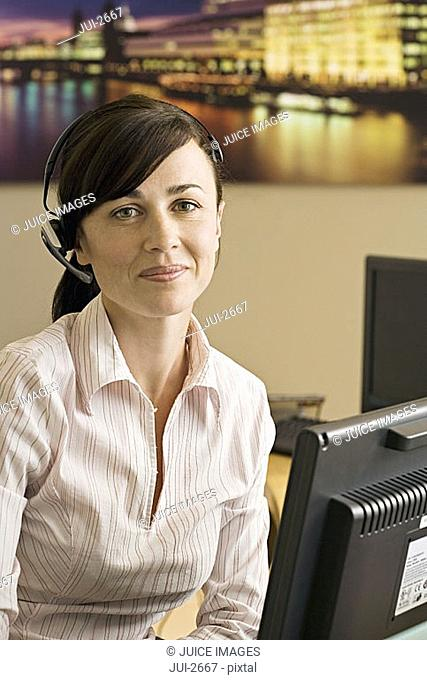 Receptionist wearing telephone headset working at reception desk, smiling, close-up, portrait