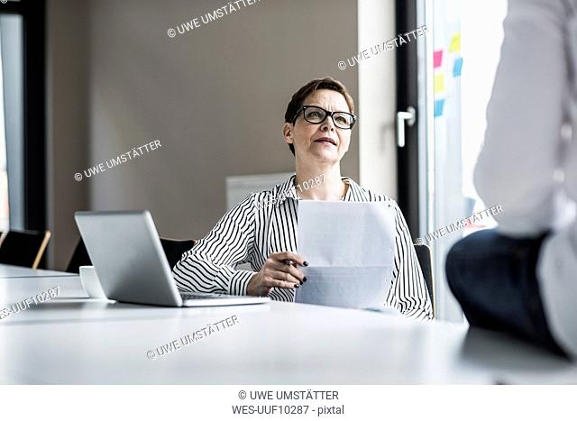 Businesswoman and businessman talking in conference room