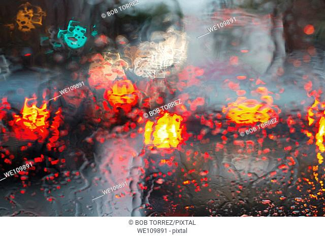 Drivers view of city traffic through rain drenched windshield