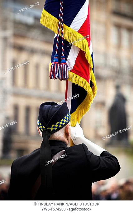 Retired soldier holding a flag at the annual Remembrance Service, George Square, Glasgow, Scotland