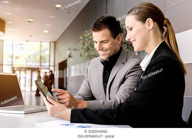 Businesswoman and businessman using digital tablet for discussion