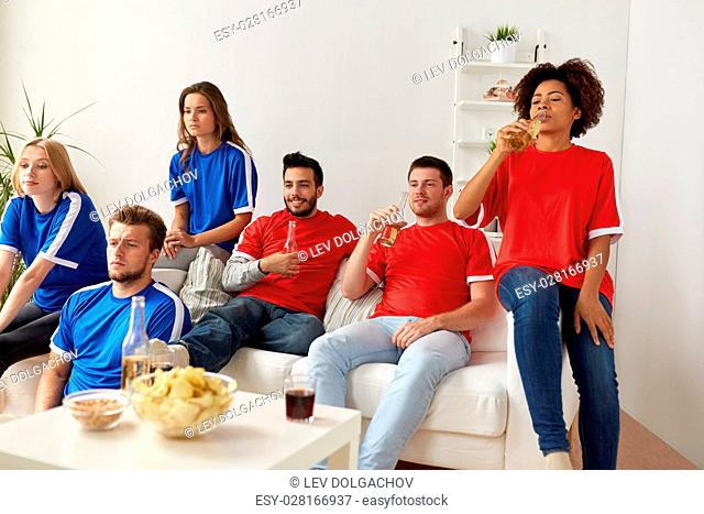 friendship, leisure, sport and entertainment concept - happy friends or football fans drinking beer watching soccer at home