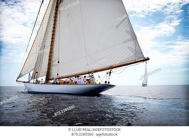Close up view of a vintage sailing boat seen from the stern with one other boat on the background. In the Mediterranean Sea on a calm day