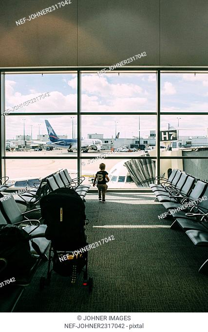 Boy looking through window at airport
