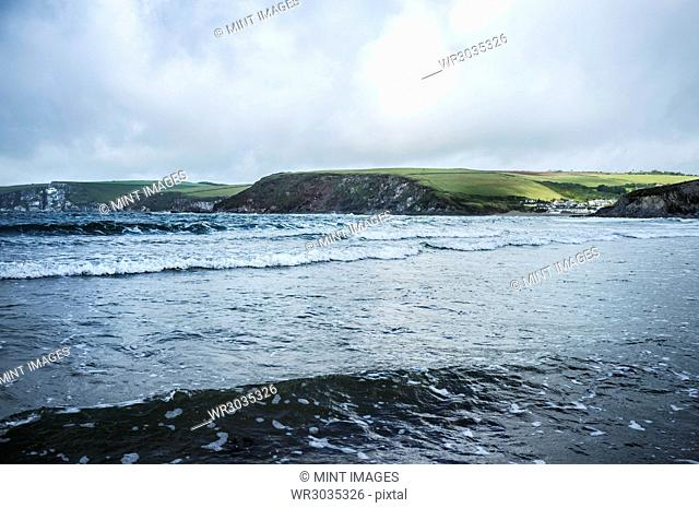 View of wave patterns in shallow choppy water, from the sea shore. Headland and coastline