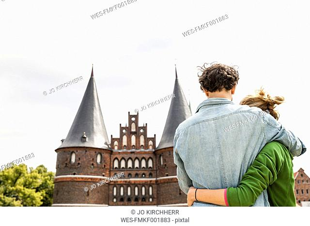 Germany, Luebeck, couple embracing in front of the Holsten Gate