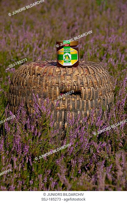 Tradional bee hives (skeps) made from straw with a glass of honey. Lueneburg Heath, Lower Saxony, Germany