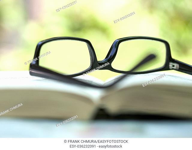 Closeup of Glasses Lying on an open Book Outdoors