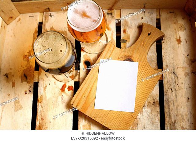 Empty note sheet on a wooden cutting board with full beer glass in a wooden crate