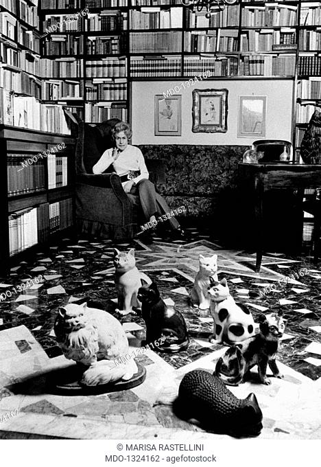Writer Gianna Manzini seated in her living room, in close-up some statues of cats. Writer Gianna Manzini is seated in her living room