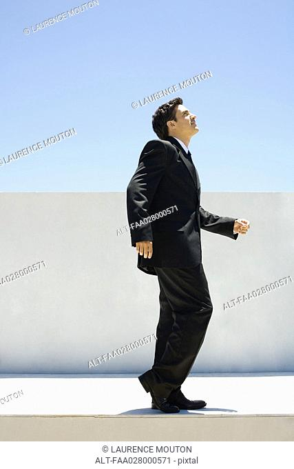 Businessman standing outdoors with one knee bent, looking up