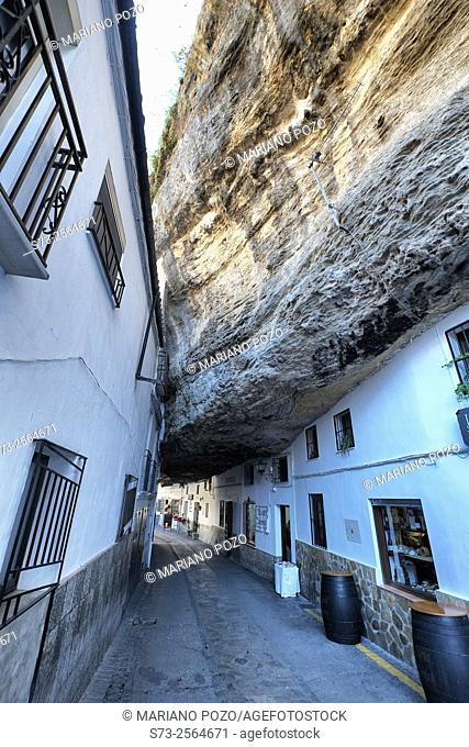 White homes constructed in caves sit under huge rocks in Setenil de las Bodegas village, Cadiz province, Andalusia, Spain