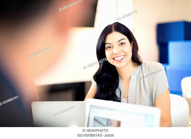Over shoulder portrait of young businesswoman at office desk