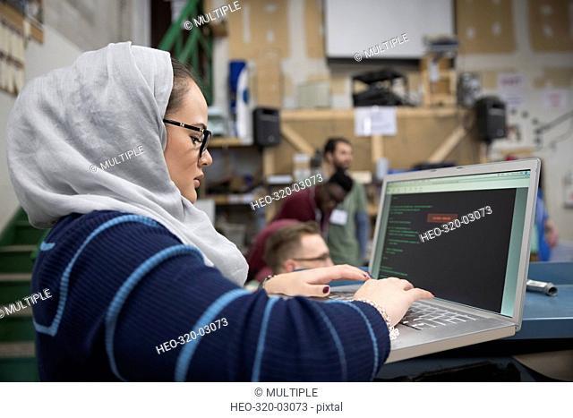Female hacker wearing hijab working hackathon at laptop in workshop