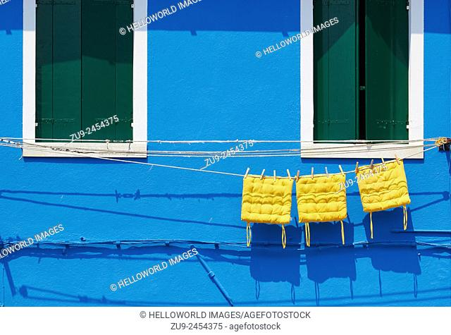 Three yellow cushions hanging on line outside blue painted house, Burano, Venetian Lagoon, Veneto, Italy, Europe