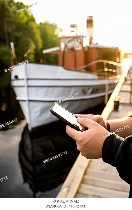 Finland, Kajaani, Man using smartphone at jetty, close-up