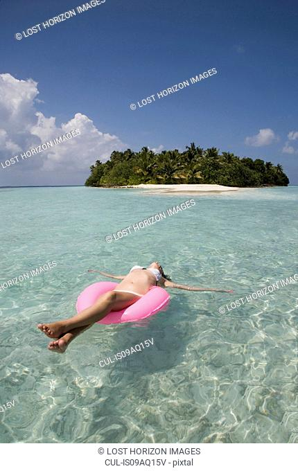 Mid adult woman floating on rubber ring in Indian Ocean, Maldives