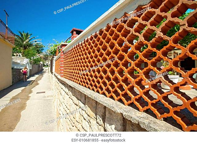 Fence made of decorative brick and stone in Susak, Croatia