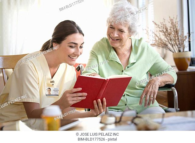 Caucasian nurse and patient reading book