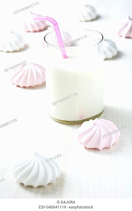 Closeup of meringues and glass of milk with pink straw on light wooden table surface