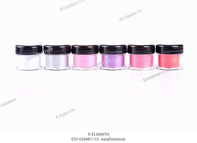 Bright mineral eye shadows in clear plastic jars, isolated on white background with natural reflection