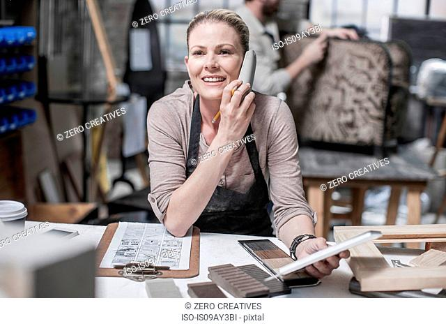 Craftswoman talking on smartphone in antique restoration workshop