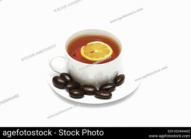 Cup of tea with lemon and chocolates isolated on white