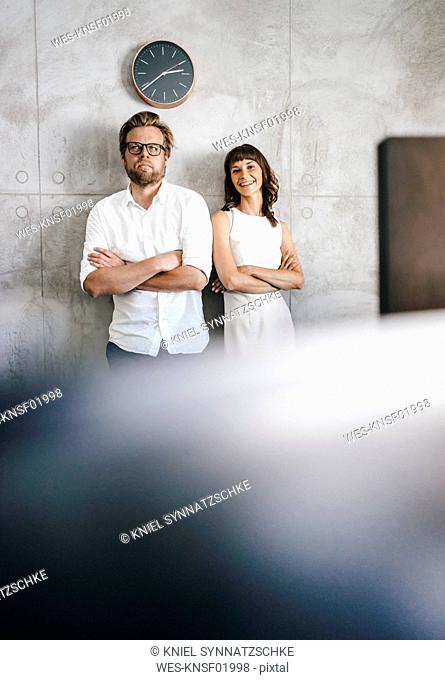 Business partners standing in office under wall clock
