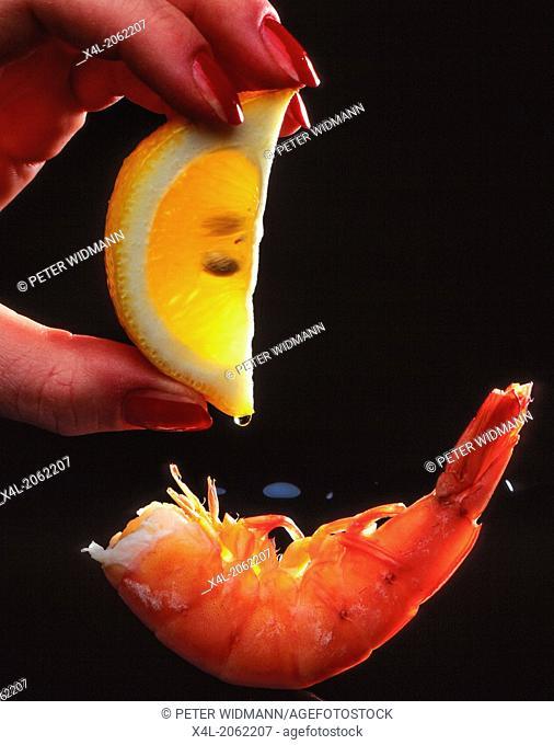 Hand squeezes lemon over fresh scampi