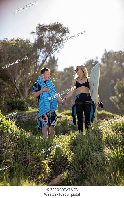Teenage boy with down syndrome and woman hand in hand with surfboard at the coast