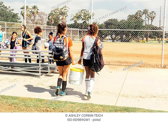 Girls and teenage schoolgirls carrying drinks cooler on school sports field