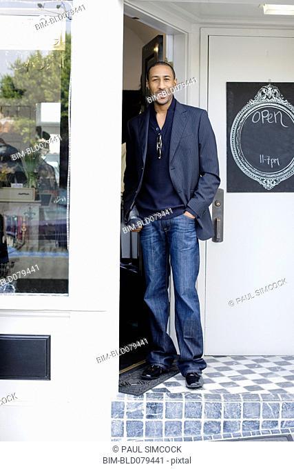 African American man standing in shop doorway