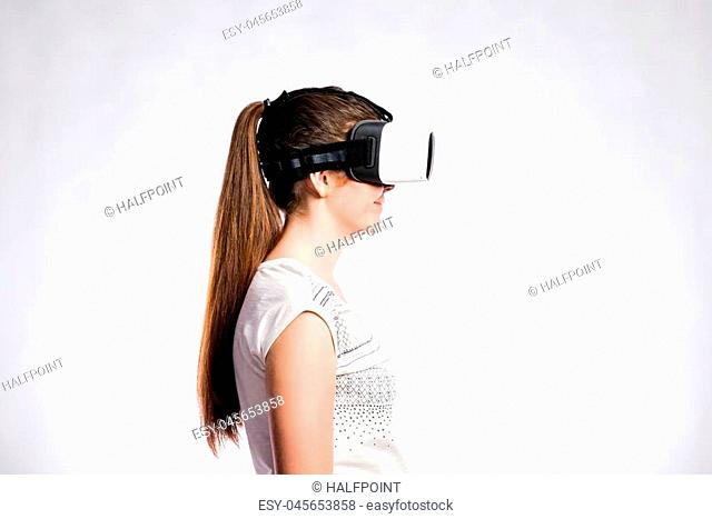 Beautiful woman in white t-shirt wearing virtual reality goggles, smiling. Studio shot on gray background