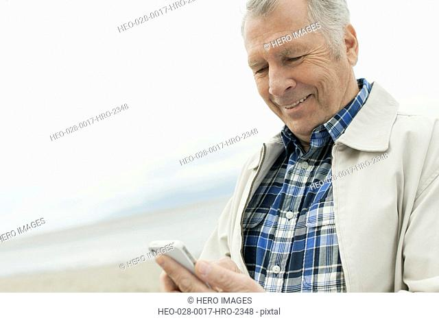 Senior man texting on smartphone by the waterfront
