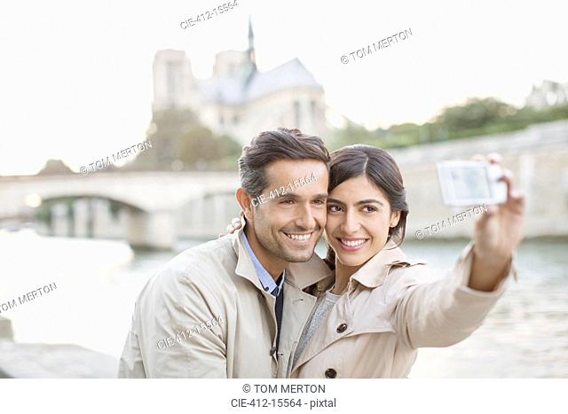 Couple taking self-portrait along Seine River near Notre Dame Cathedral, Paris, France