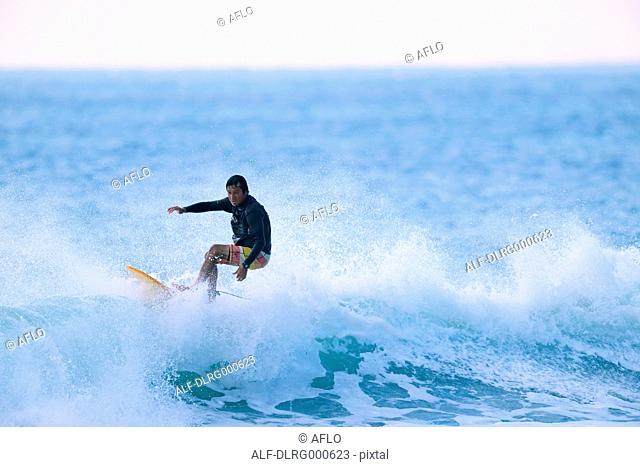 Japanese surfer riding wave
