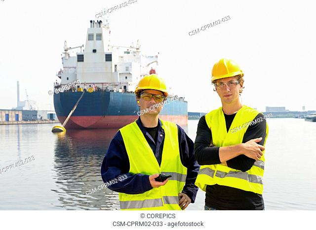 Portrait of two dockers, posing in front of a large moored oil tanker in an industrial harbor