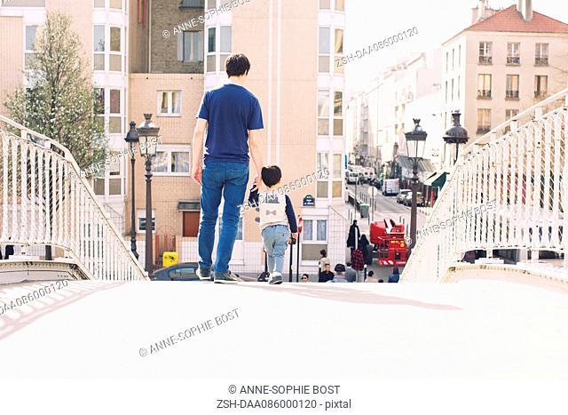 Father and little boy walking on bridge