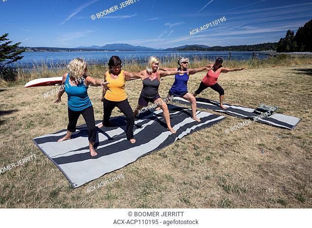 Five female friends practice Yoga while camping on Quadra Island, Canada