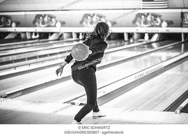 Young Woman Approaching Lane with Ball at Bowling Alley