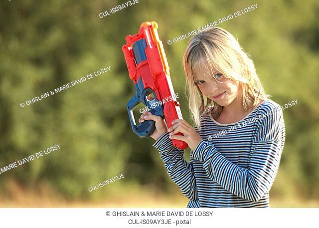 Portrait of girl holding water gun, Buonconvento, Tuscany, Italy