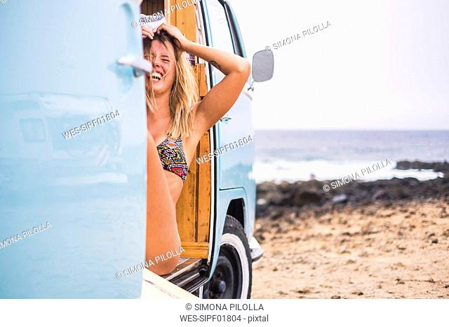 Laughing young woman in van on the beach