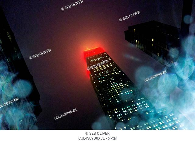 Low angle view of skyscraper illuminated at night, New York, USA