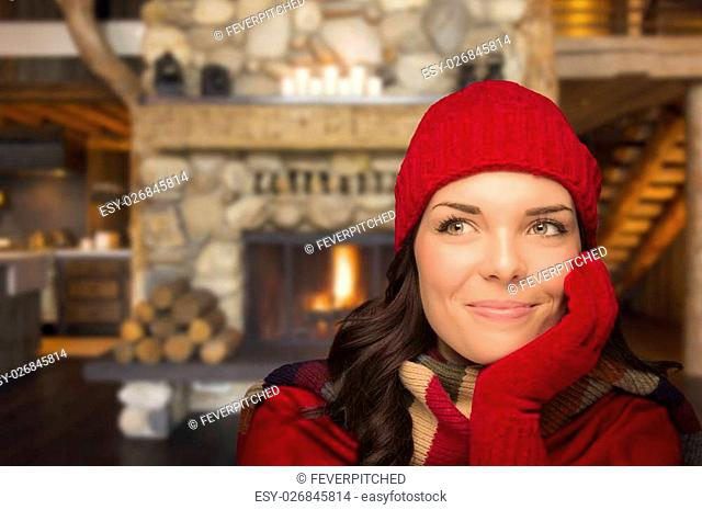 Smiling, Comfortable Mixed Race Girl Looking To The Side Enjoying Warm Fireplace In Rustic Cabin