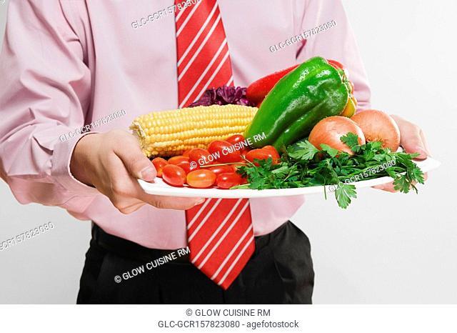 Businessman holding a platter of fresh vegetables