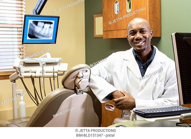 Black dentist smiling in office