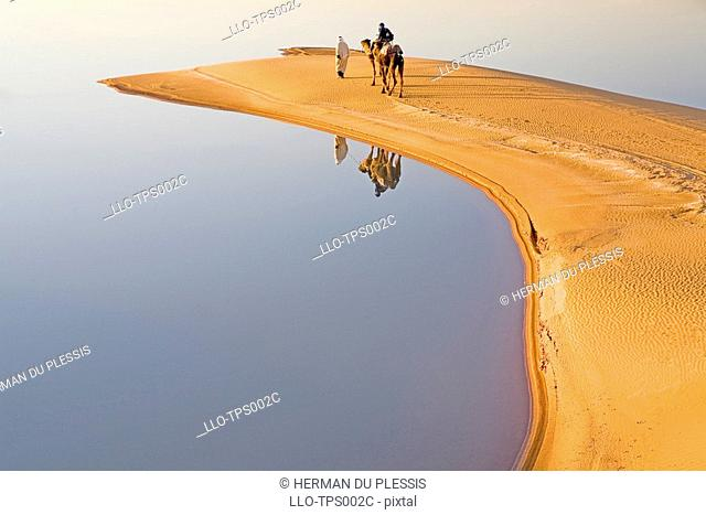 Reflection of Berber Man with Tourist on a Dromedary Camel Camelus dromedarius  Merzouga, Erg Chebbi, Sahara Desert, Morocco, North Africa